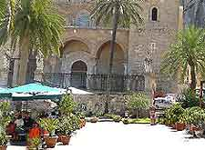 Photo of tourists enjoying a sunny outdoor lunch next to the cathedral of Cefalu, Sicily